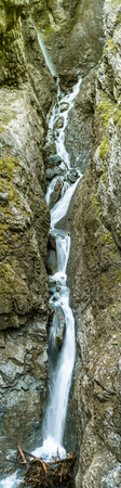 vertical panorama of a long waterfall in a narrow gorge in the Swiss Alps