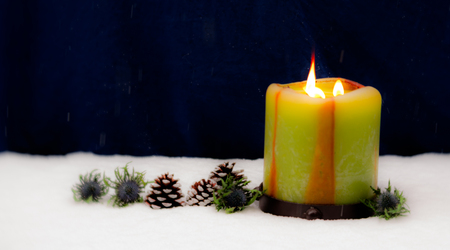 beautiful Christmas atmosphere with candle and pine cones and blue flowers during snow fall at night