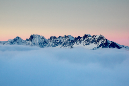winter mountain landscape above the clouds in the Swiss Alps at sunset