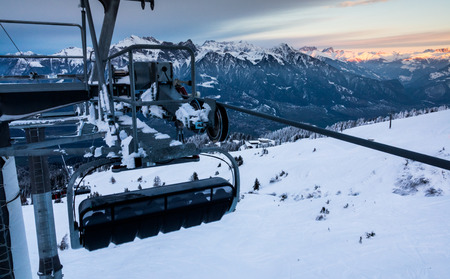 chairlift in a ski resort with winter mountain landscape behind at sunset