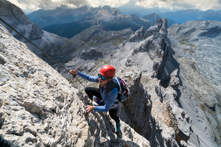 young female climber on a steep Via Ferrata in the Italian Dolomites with a great view Stock Photo