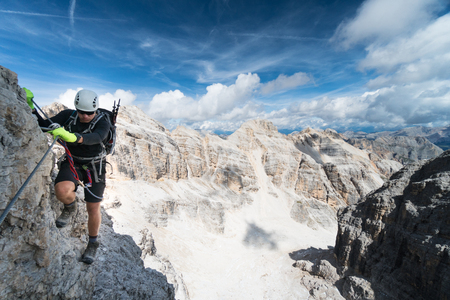 young male climber on an exposed Via Ferrata in the Dolomites with a fantastic view of the surrounding mountains