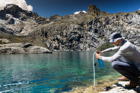 male mountain climber filtering drinking water from a turquoise mountain lake high up in the Andes in Peru