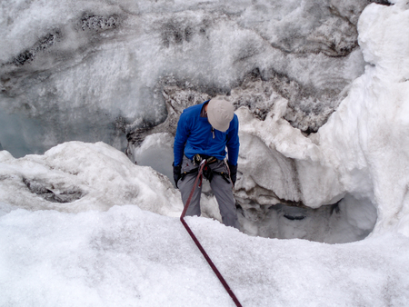 male mountain climber victim in a glacier crevasse during a training exercise