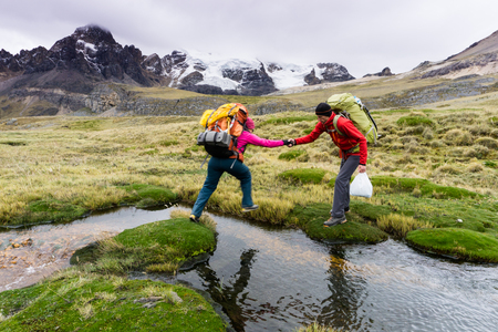 man mountain climber helps female climber cross a small mountain stream in the Andes in Peru Stock Photo