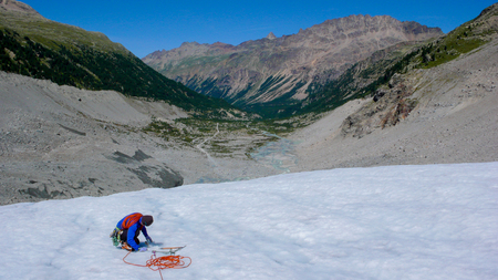 male mountain guide during a crevasse rescue training exercise on a glacier in the Alps