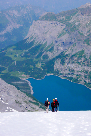 mountain guide with two clients descending a steep white glacier with a fantastic blue mountain lake far below Banque d'images