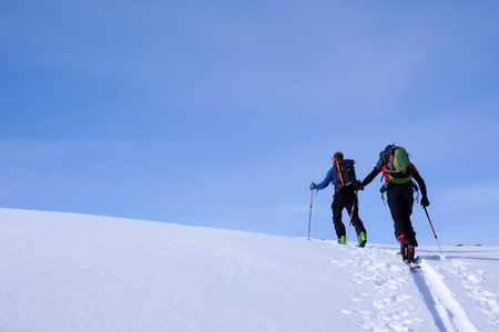 mountain guide on backcountry ski tour leading a client to the peak of a high alpine mountain