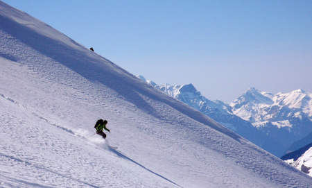 backcountry skier skiing really fat down an untouched mountain side with loads of fresh powder snow