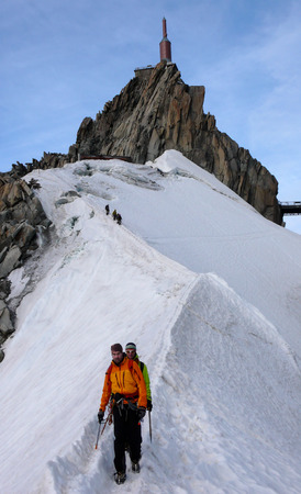 Mountain guide and a male client on a rocky ridge heading towards a high summit in the French Alps near Chamonix