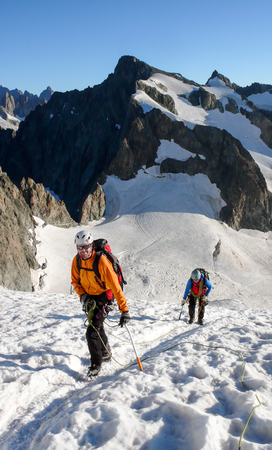 mountain guide and client heading up a glacier towards a high alpine summit on a beautiful summer morning Stock fotó