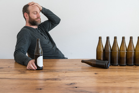 man with a beard and hangover and a drinking problem looks at many empty beer bottles