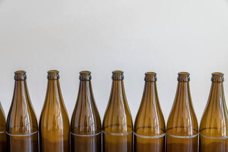 close up view of many empty beer bottles in a row