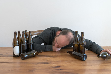 horizontal view of an alcoholic middle-aged man with head on the table  and many empty beer bottles Banque d'images