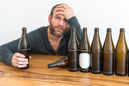 horizontal view of an alcoholic middle-aged man and many empty beer bottles