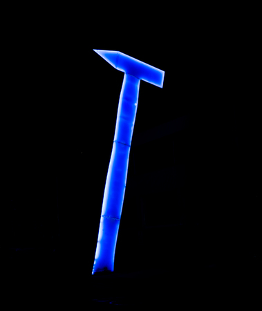 huge and tall blue neon hammer in the dark night Stock Photo
