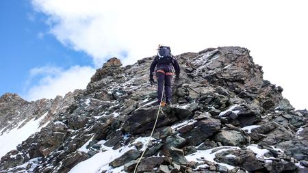 mountain guide climbing a rocky ridge towards a far away peak Stock Photo