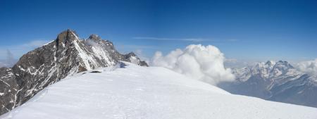 panorama mountain landscape in the Swiss Alps near Zermatt on a beautiful day in late winter under a blue sky