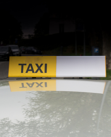 taxi sign on the roof of a gray car Stockfoto