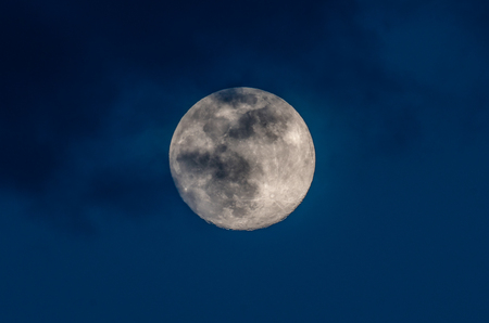 gorgeous full moon in a dark blue night sky gets covered by soft wispy dark clouds