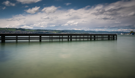 wooden pier on lake Zurich with rolling hills mountain landscape and sailboats in the background 免版税图像