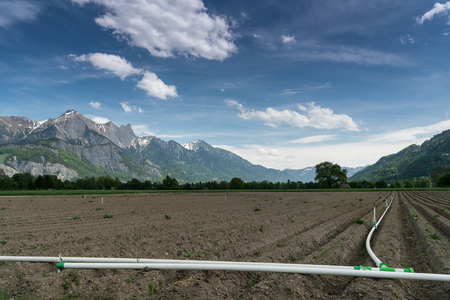 freshly plowed field with a clever irrigation system and a beautiful mountain landscape behind
