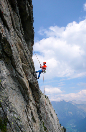 male rock climber abseiling off a steep rock climbing route in the Swiss Alps after a hard climb