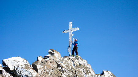 male backcountry skier at the summit cross of a high alpine peak on a beautiful winter day 写真素材