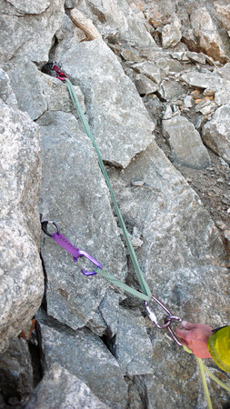 mobile protection and an improvised belay stance on a granite rock climbing route up close