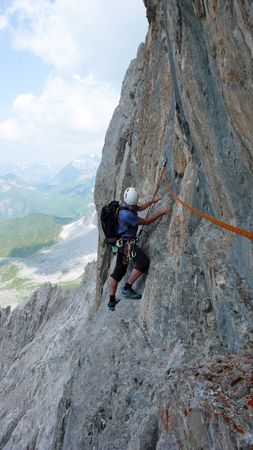 male mountain climber on a steep rock climbing route in the Swiss Alps near Klosters