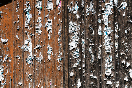 wooden barn doors with staples and remains of torn off posters Фото со стока
