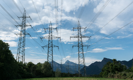 power lines and pylons in silhouette against a blue sky with white clouds and trees below