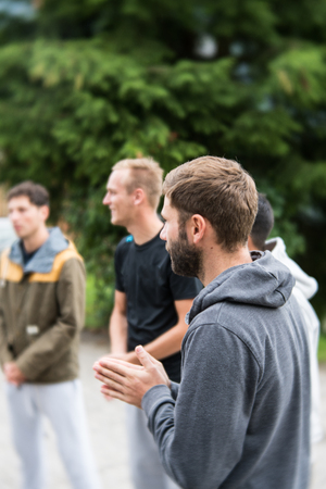 young group of men stand in a circle and prepare to have a group prayer outdoors