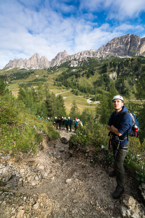 young male climber looks up at a Via Ferrata in the Dolomites in Alta Badia with great landscape and group of climbers behind him