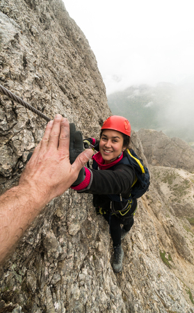 young attractive female mountain climber in the Dolomites of italy giving her guide a high five for success Stock Photo