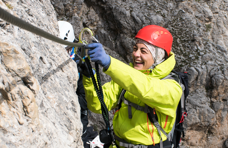 young  female mountain climber on a Via Ferrata in the Dolomites in Alta Badia clicking carabiners in the cable for safety and smiling