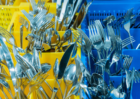 silverware and cutlery in colorful palstic ocntainer in an industrial restaurant kitchen 写真素材