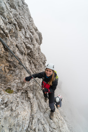 young attractiv climbers on a vertical and exposed rock face climbs a Via Ferrata while smiling and pointing to a faraway mountain peak