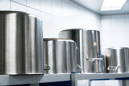 row of large metal cooking pots in an industrial size restaurant kithcen on a metal shelf