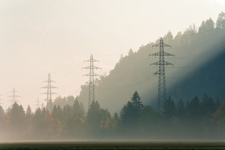 power lines and lattice crosses on a hazy morning in a mountain valley with fall color forest all around Stock Photo