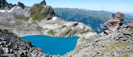 panorama mountain landscape in the Swiss Alps with a great view and a turquoise lake in the center