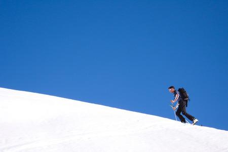 man hiking up a snowy mountain with skis underneath a blue sky in winter in the Swiss Alps Stock Photo