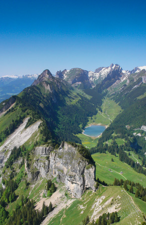 mountain landcape in the Alpstein region of Switzerland with jagged peaks and a pristine blue mountain lake in the valley far below
