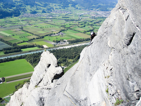 rock climber on a steep and exposed limestone climbing crag in the Swiss Alps above lush green fields below