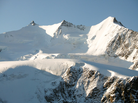 Mischabel mountain range in the Swiss Alps above Saas Fee on a beautiful late fall evening under a blue sky