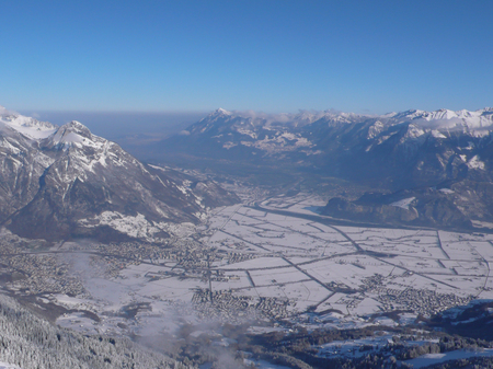 view from a high alpine mountain peak in Switzerland with a great view of the valleys and villages and mountains behind all covered in wonderful winter white snow