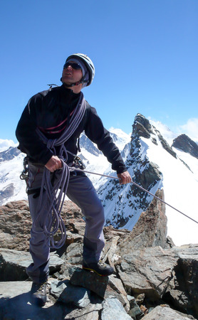 mountain guide standing on a rocky mountain peak and pulling a client up on a rope with a fantastic mountain landscape of the Swiss Alps behind him Фото со стока