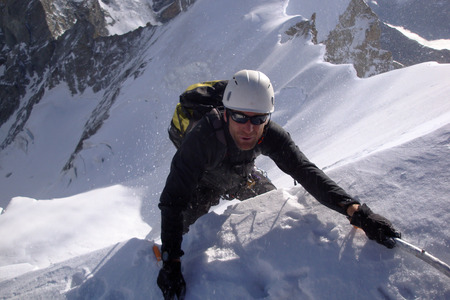 mountain climber reaches the edge of a summit ridge and exits a steep north face in windy and nasty weather in the Swiss Alps 免版税图像