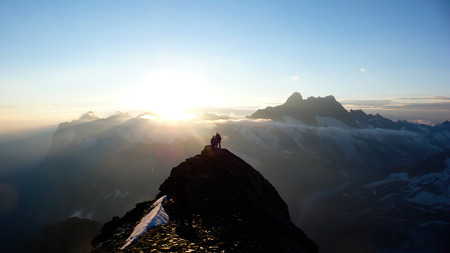 mountain climbers on a rocky ridge at sunrise climbing Eiger mountain in the Swiss Alps