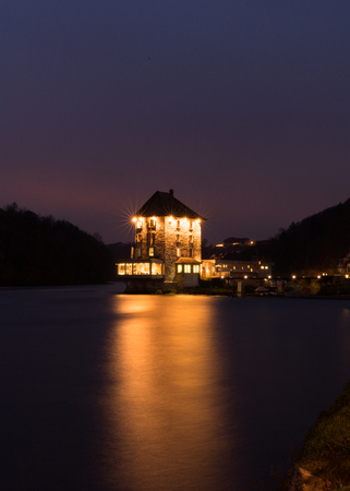 nightfall and dusk on the Rhine Falls and Rhine River with an illuminated castle building on the water Editöryel